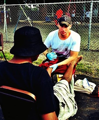 Senior Andrew Enslen, as a Happy Feet Clinic volunteer, washing a man's feet in August 2013. (Photo by Miles Miller)
