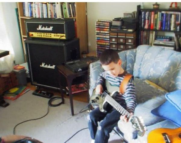 Mike Holland at 6 or 7 years old playing on a guitar that was his dad's at the time. During Holland's senior year of high school, his dad passed the guitar on to him. He is using it for one of his new tracks. (Photo Courtesy of Mike Holland)