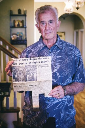 John Skelly hold a newspaper clipping headlining his involvement in the Selma march.