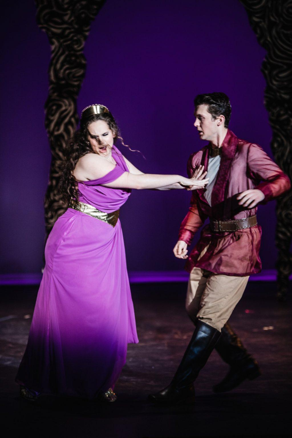 Dido, Queen of Carthage (Withers), pushes away her Greek love Aeneas (Joe Hebel). The opera follows the tragic journey of the couple's struggle between love and prophesy.