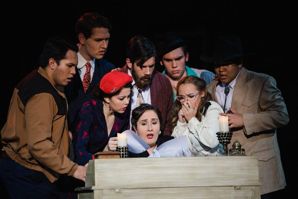 "The cast of ""Gianni Schicchi"" gathers around Zita (Hannah Miller) as she reads the will of their late relative. The uniquely small size of the ""Schicchi"" cast provided extensive learning opportunities for the students and fostered a tight community."
