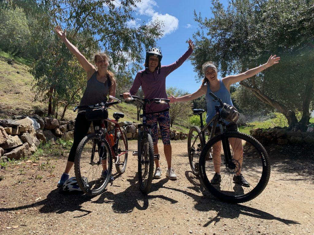 Off-campus seniors Grace Palmer, Cori Persinger and Kelsey Harmon, who are quarantining together, bike on a trail near Calamigos Ranch during campus closure.
