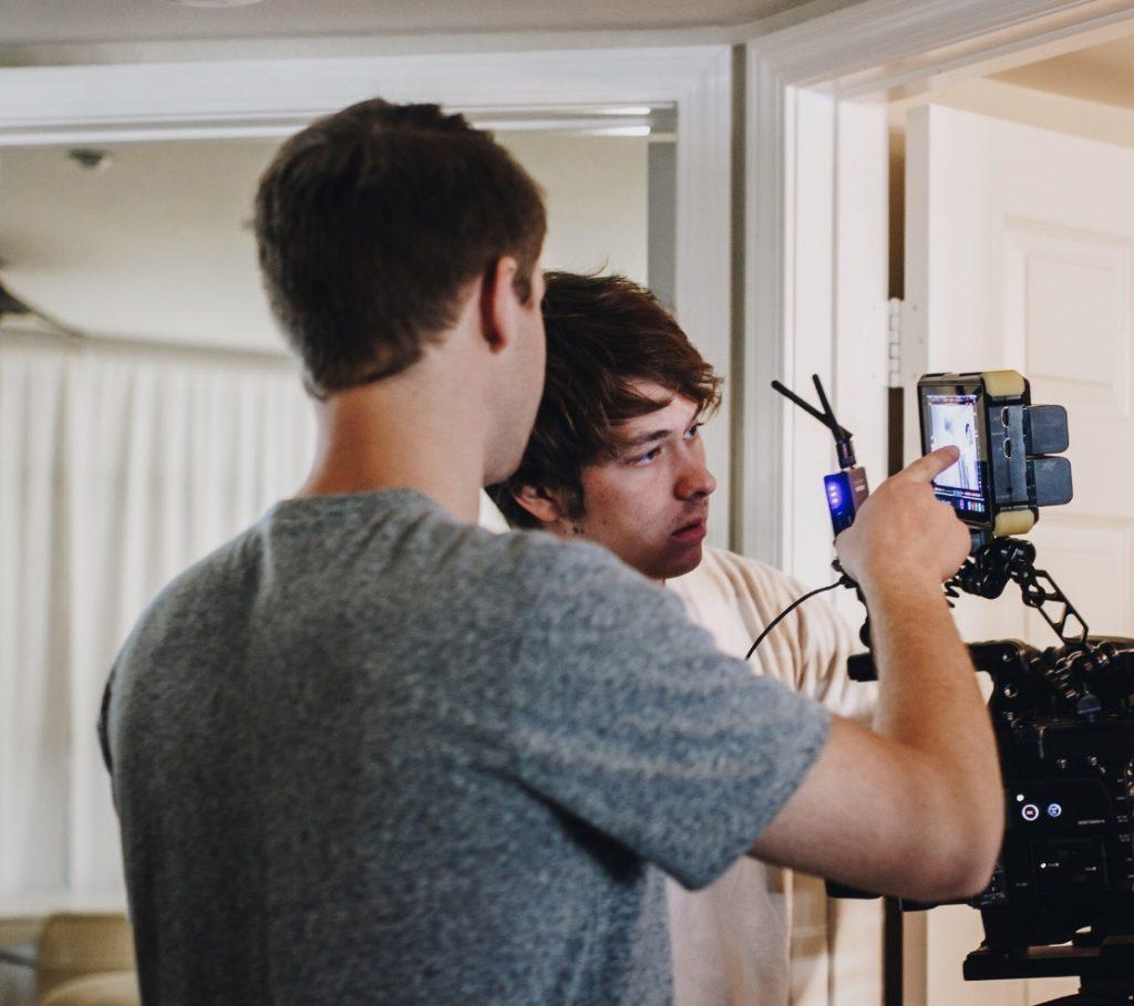 "Battin (right) and senior Orion Keen (left) analyze a frame in an LED monitor. This picture was taken on the first day of shooting for the film ""Self-Absorbed."""