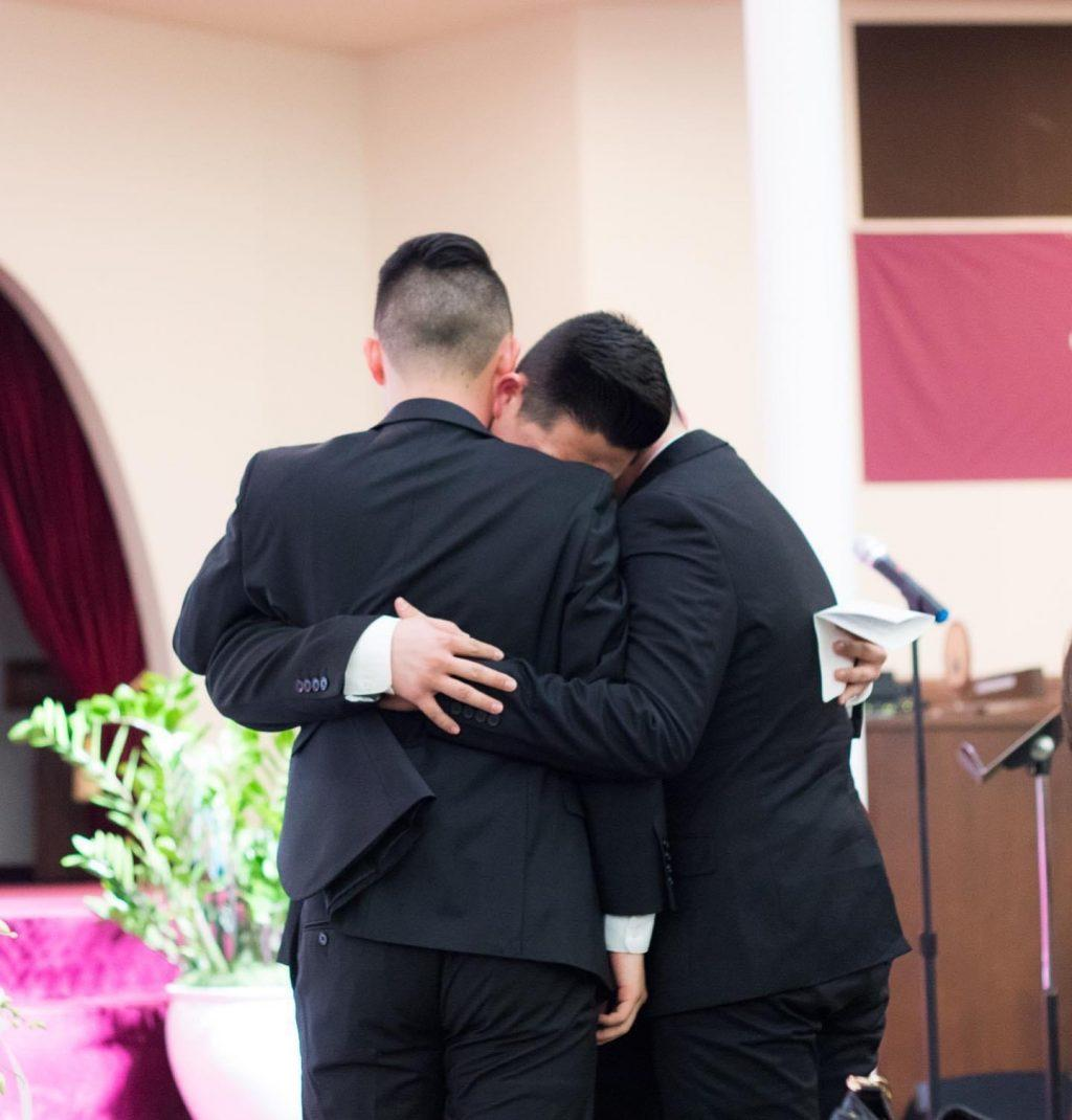 Justin and his brothers Brandon and Dylan embrace each other at their father's funeral.