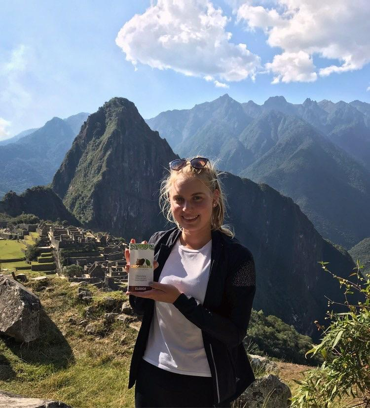 Chocolatier and founder Anastasia Lamachkine shows off her Choconastu chocolate bar atop Machu Picchu, Peru. Her chocolate is made with organic cacao beans from Tingo Maria, a city located in the Peruvian rainforest. Photo courtesy of Anastasia Lamachkine