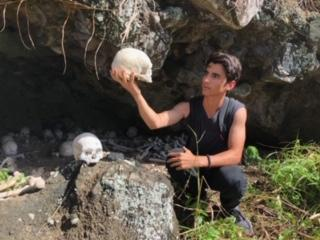 Fiji program attendant Brandon Oddo gazes at an unidentified skull before an entrance to a cave during his visit to Fiji. While in the abroad volunteer program, Oddo visited a variety of interactive settings and connected with the locals on a personal level.