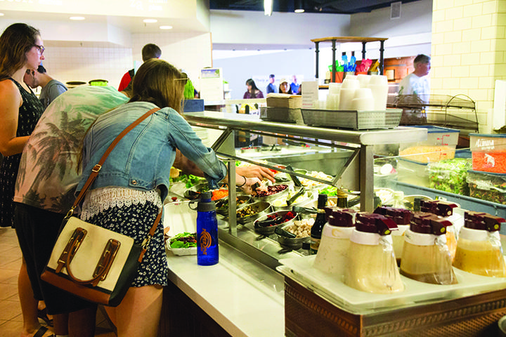 Students reach for toppings at the then-self-serve salad bar. Stations and bars that were self-serve are no longer permitted in the cafeterias across campus. File photo