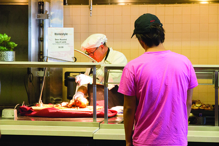 A hungry student watches a Waves Cafe cook prepare a meal. Pepperdine Dining Services announced any meal service for on-campus students will be from Seaver Campus's cafeteria but may provide a few new ways to distribute food. File photo