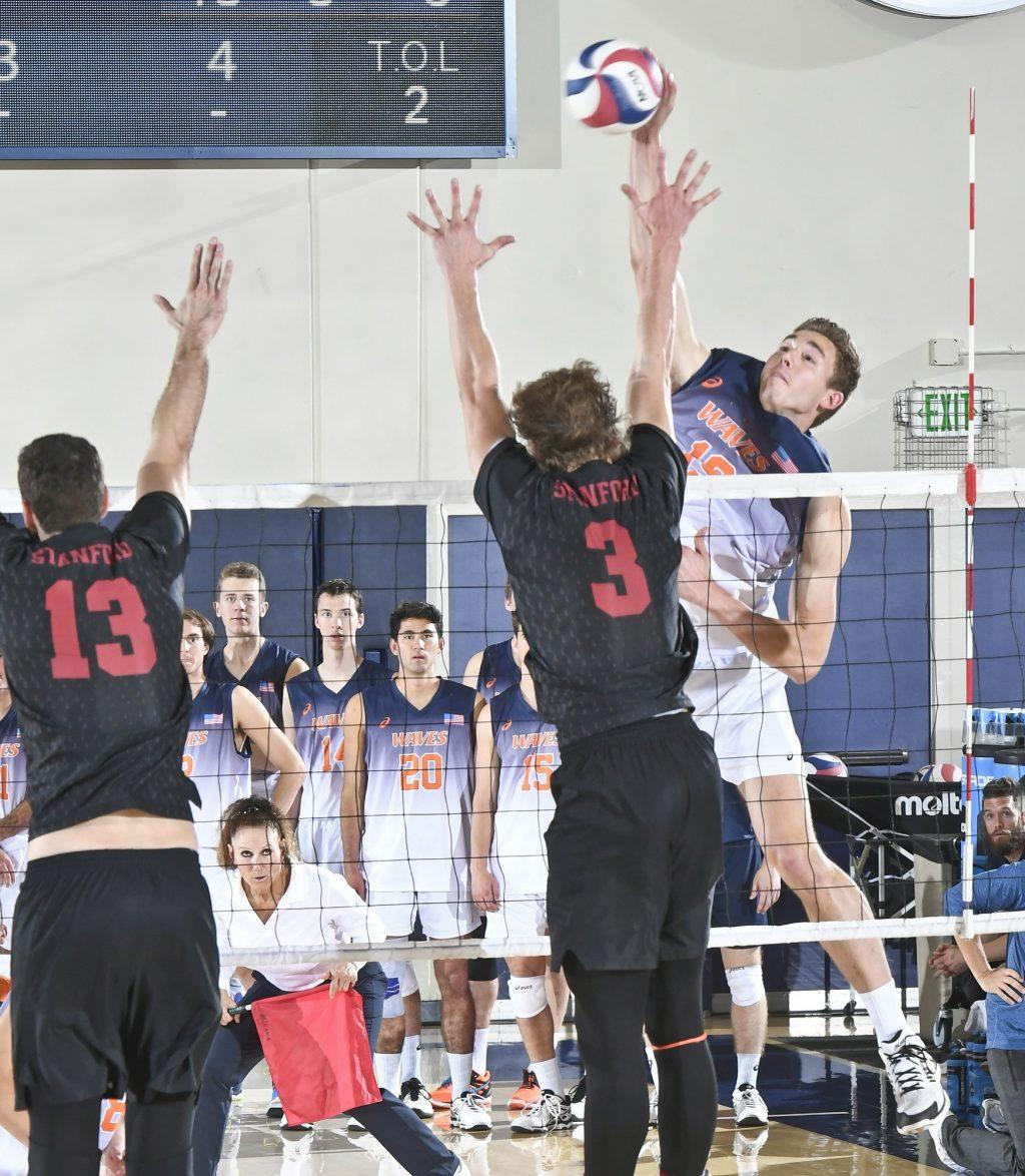 Pepperdine outside hitter David Wieczorek takes a swing against two Stanford blockers in a Feb. 8, 2019 MPSF match at Firestone Fieldhouse. Photo courtesy of Pepperdine Athletics