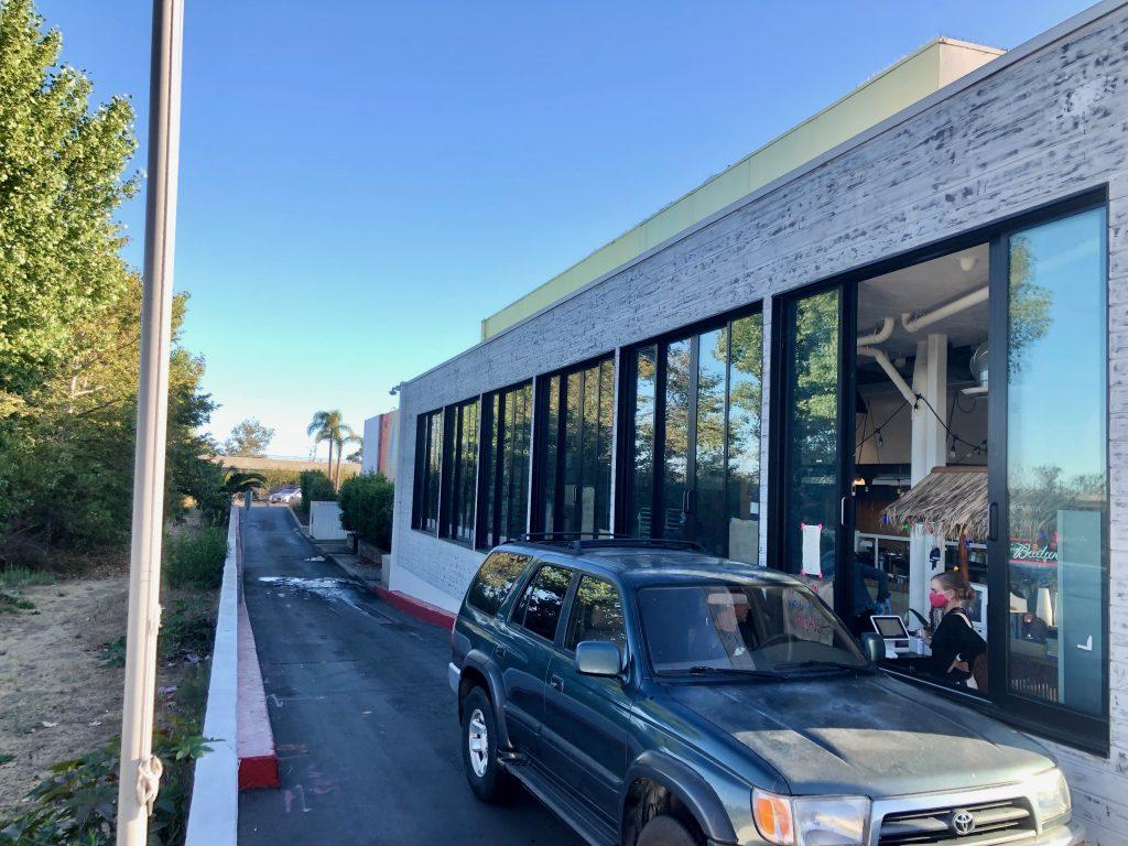 A patron orders and picks up his food from inside his car at Broad Street Oyster Company's recently opened drive-thru window.