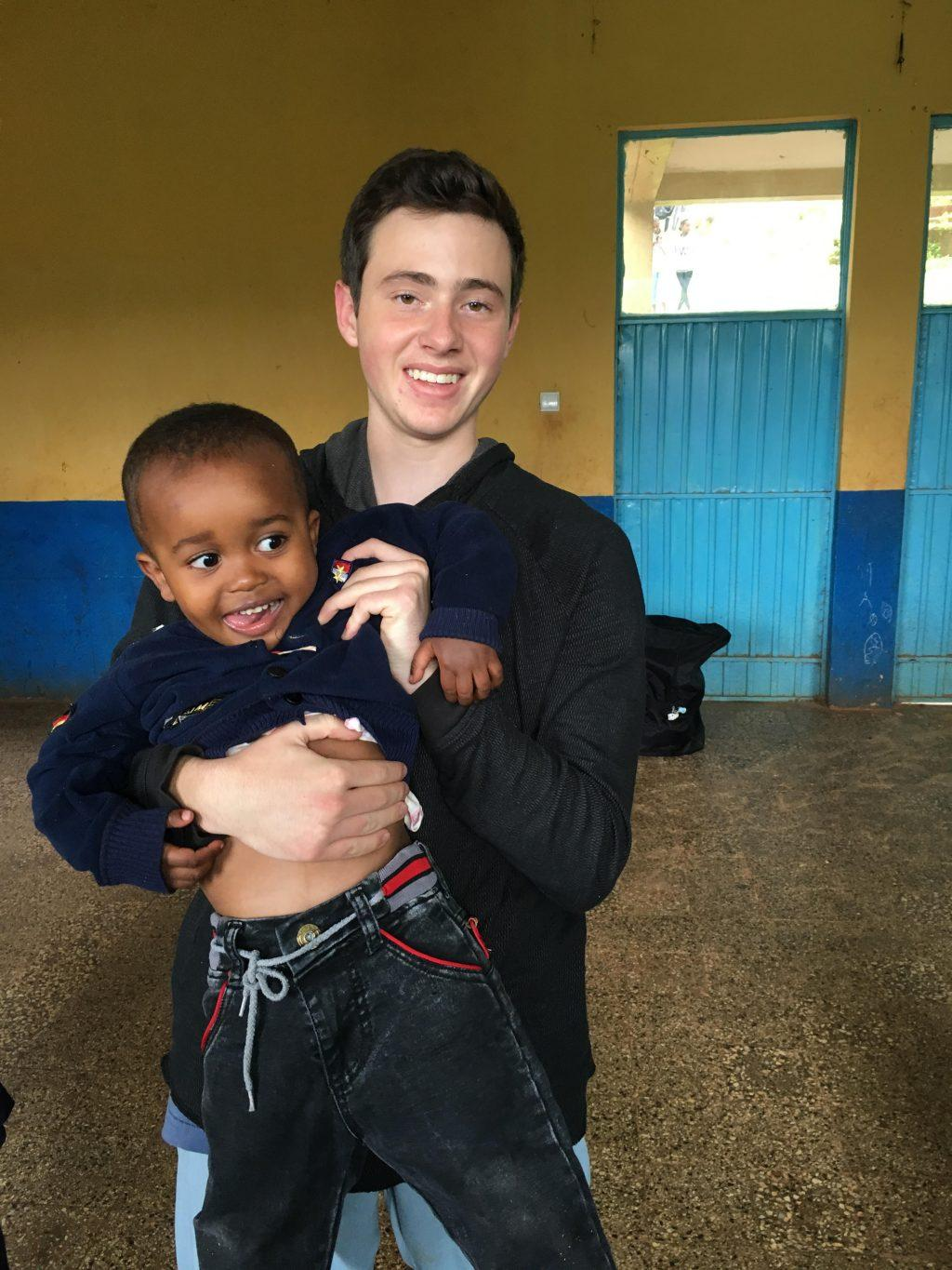 Ishak smiles with an Ethiopian child at an orphanage. He visited the country on a medical mission trip with his family.