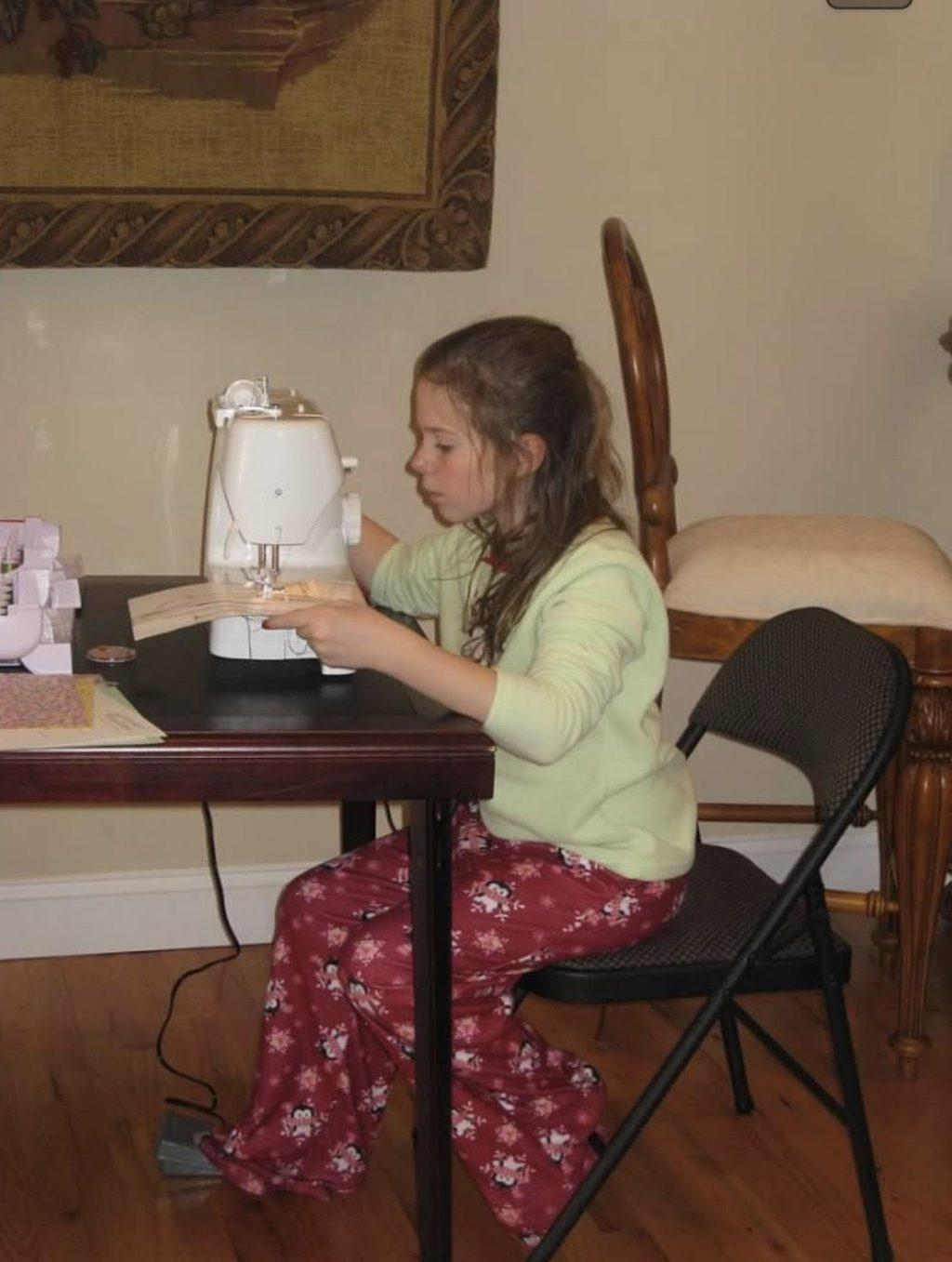 Murphy sits at a table with her first sewing machine, which she got when she was a child. She has been sewing for at least 10 years.