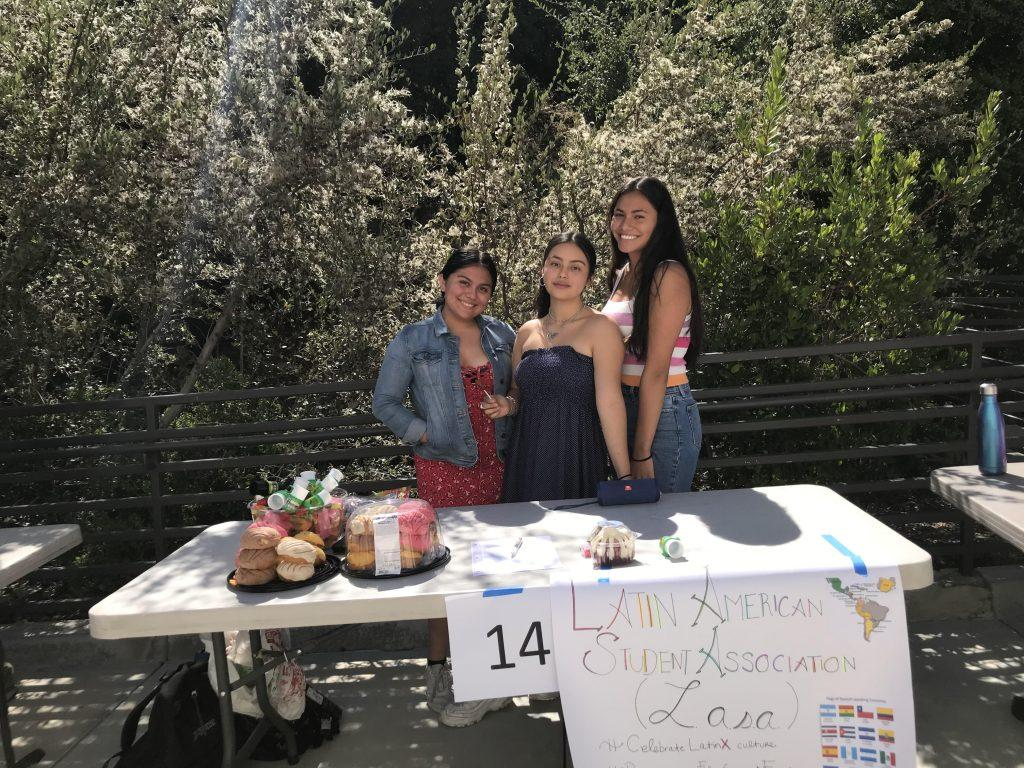 Taura (far right) and her fellow co-presidents stand behind their booth for the Latin American Student Association at their high school club fair. Taura handed out pastries and candy while encouraging fellow students to join the club.