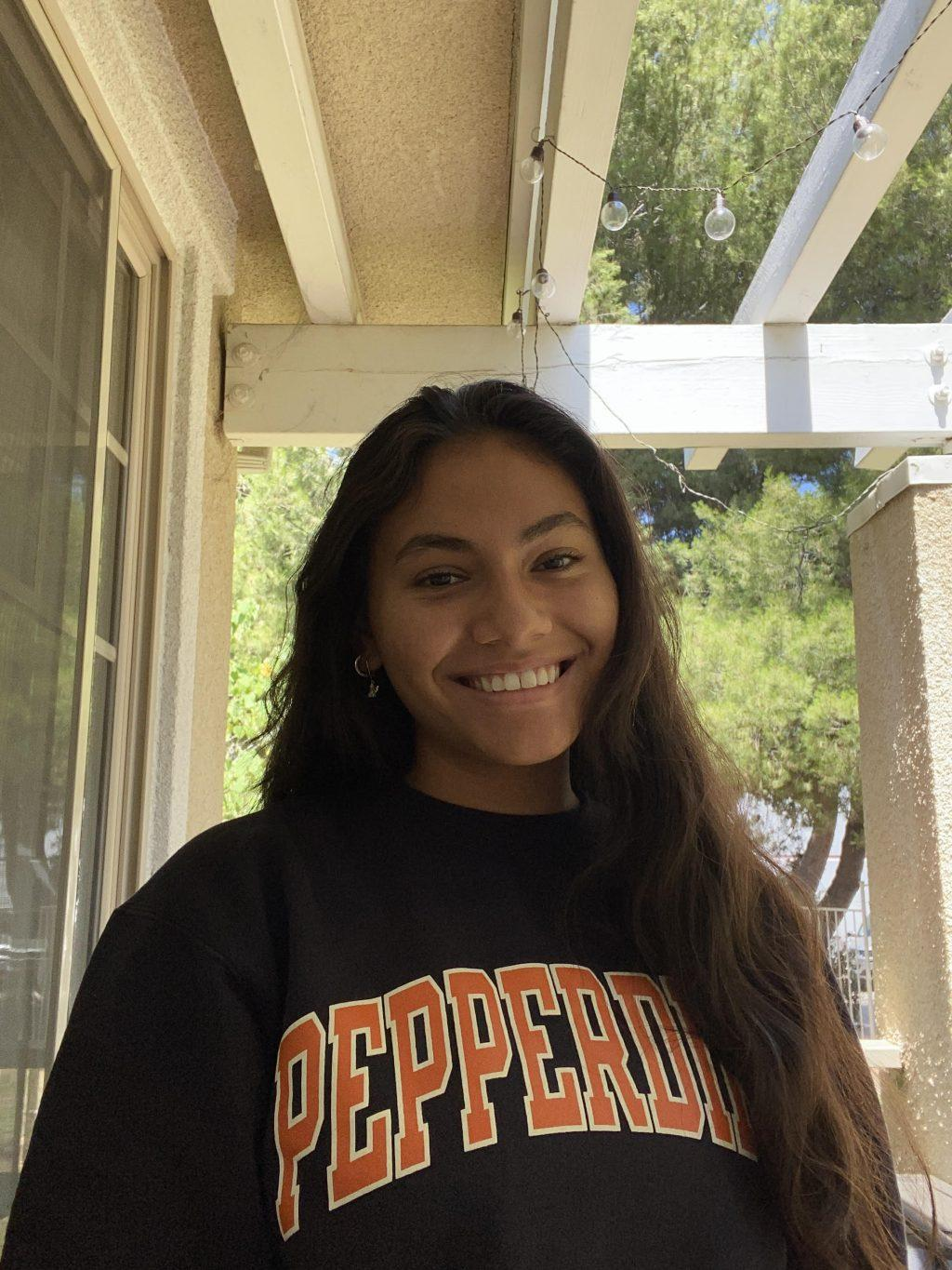 A cheerful Taura reps her university's sweatshirt outside of her home. She said she expressed joy about her acceptance.