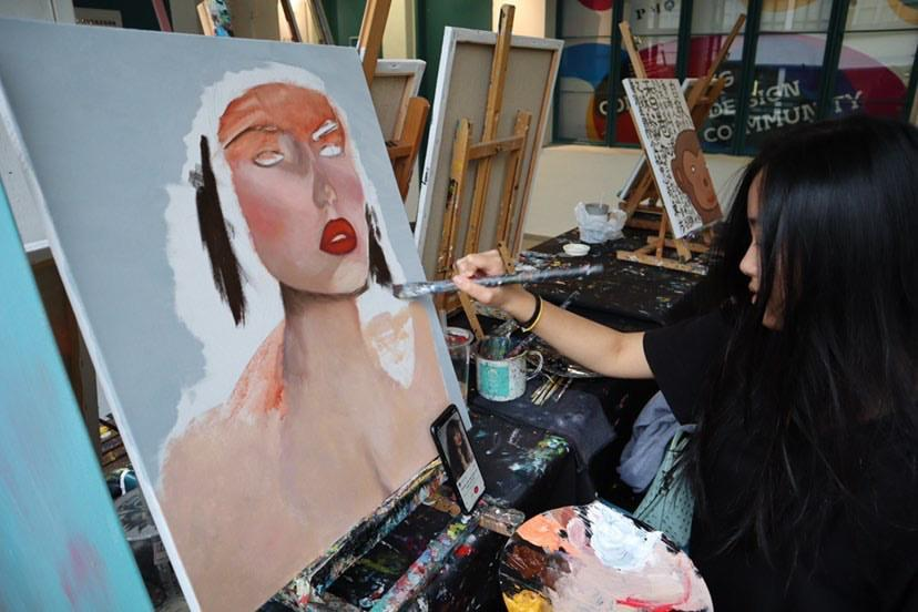 Keung paints an original portrait. During the summer, Keung and her friends painted and traveled throughout Hong Kong.