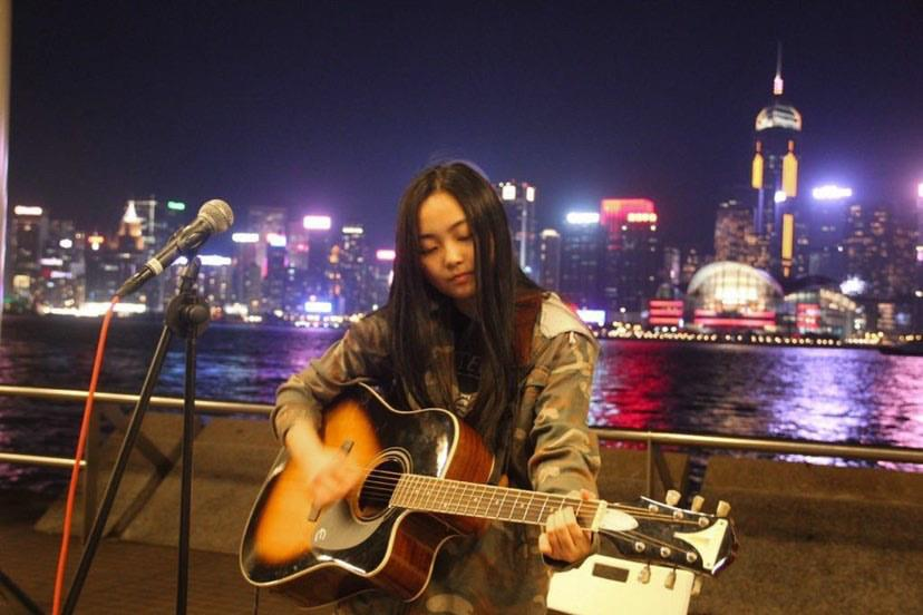 Keung plays guitar while performing on the street in Hong Kong. Before the COVID-19 pandemic took full effect, Keung and her friends would often busk and play music at local bars.
