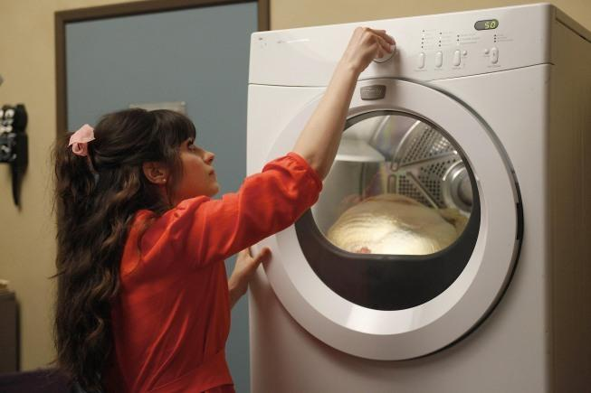Jess, played by Zooey Deschanel, loads a frozen Thanksgiving turkey into the dryer. The holiday's main entree did not fit into the apartment's oven. Photo courtesy of IMDb