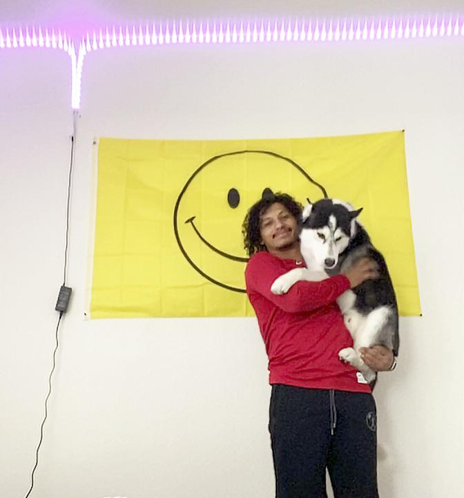 McAfee cradles his husky, Halo, in front of a smiley-face flag in his Arizona apartment on Sept. 15. He said the flag is the first thing he looks at every day, which makes him smile. Photo by Ali Levens