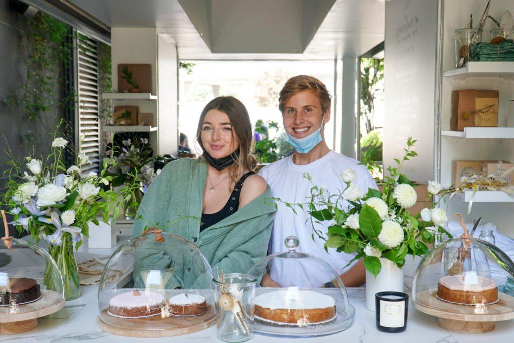 Johnson and coworker Ashling Sugarman stand behind a plethora of baked goods at the Little House Confections pop-up shop. They have displayed their specialty cake, the Bomb Ass Olive Oil Cake, which has gone Internet famous. Photo courtesy of Chase Johnson