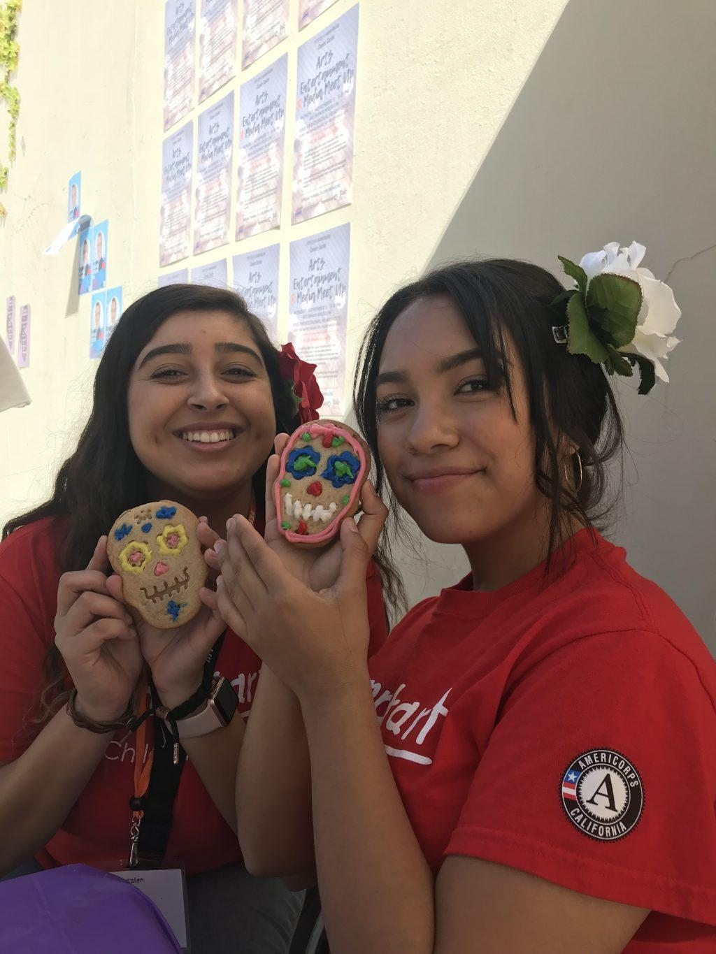 Celeste Benitez (right) decorates a colorful Día de los Muertos cookie with her friend and fellow LSA member Madalen Carrera on campus in November 2018. The pair tabled by the Rock on the Malibu Campus to promote the LSA's Noche de Altares (Night of the Alters) event. Photo courtesy of Celeste Benitez