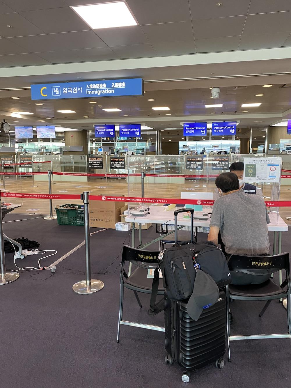 A quarantine-facilitating official checks a man's forms in the Incheon International Airport in South Korea. The man sat with his luggage at the second station at 5:20 p.m.