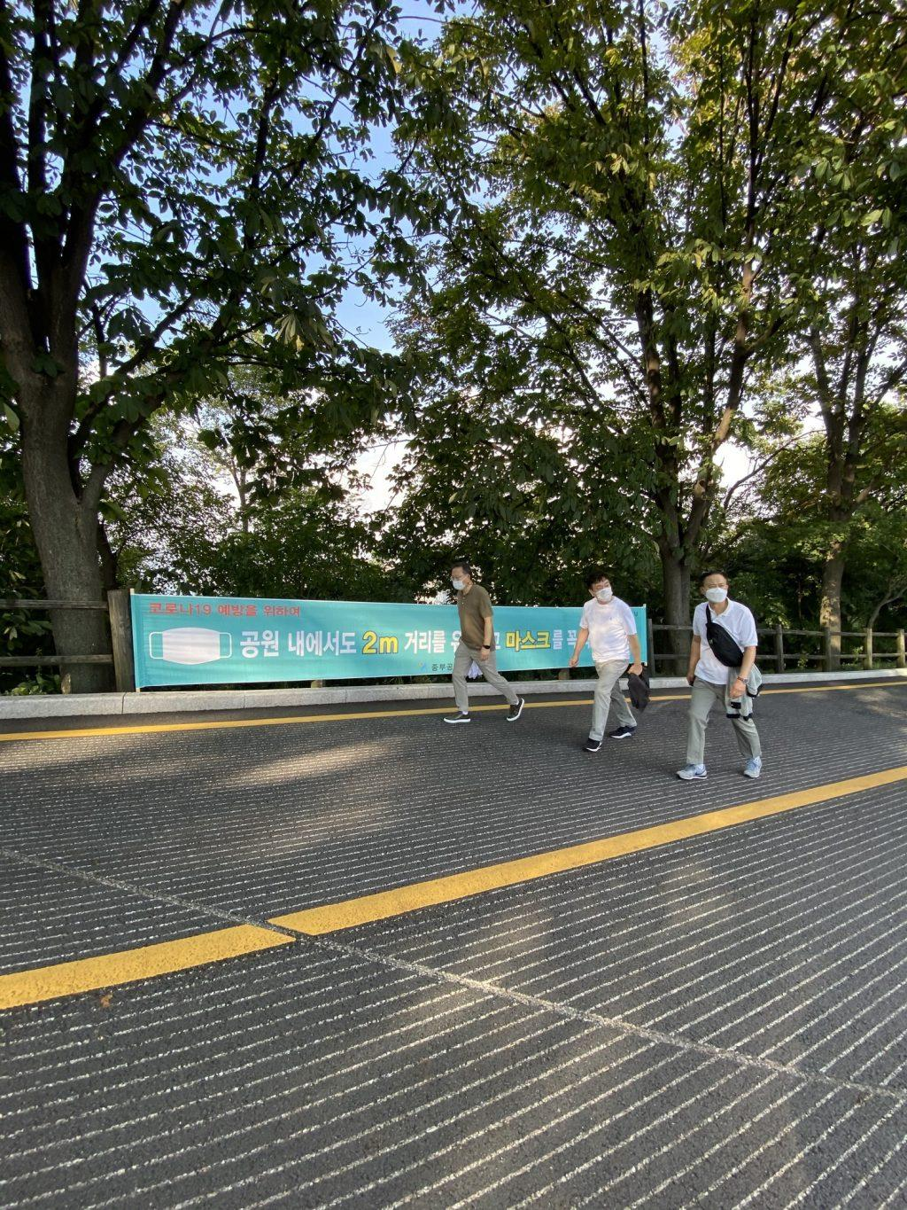 Three men wear masks while walking in front of a banner that reminds the public of the COVID-19 precautions. Similar forms of this banner were placed along both sides of the road with occasional hand sanitizers on small stools.