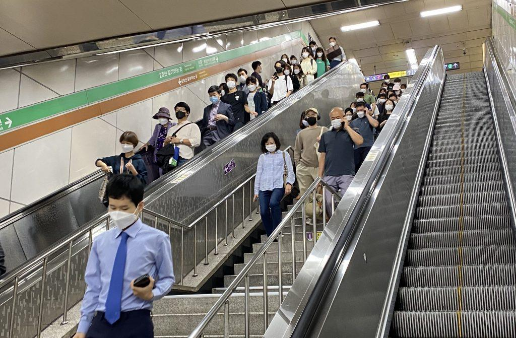 A crowd of public-transit users exit one subway and transfer to another subway line at Hapjeong Station. People continued to wear face masks Sept. 25, which was almost two weeks after the social distancing level was brought down.