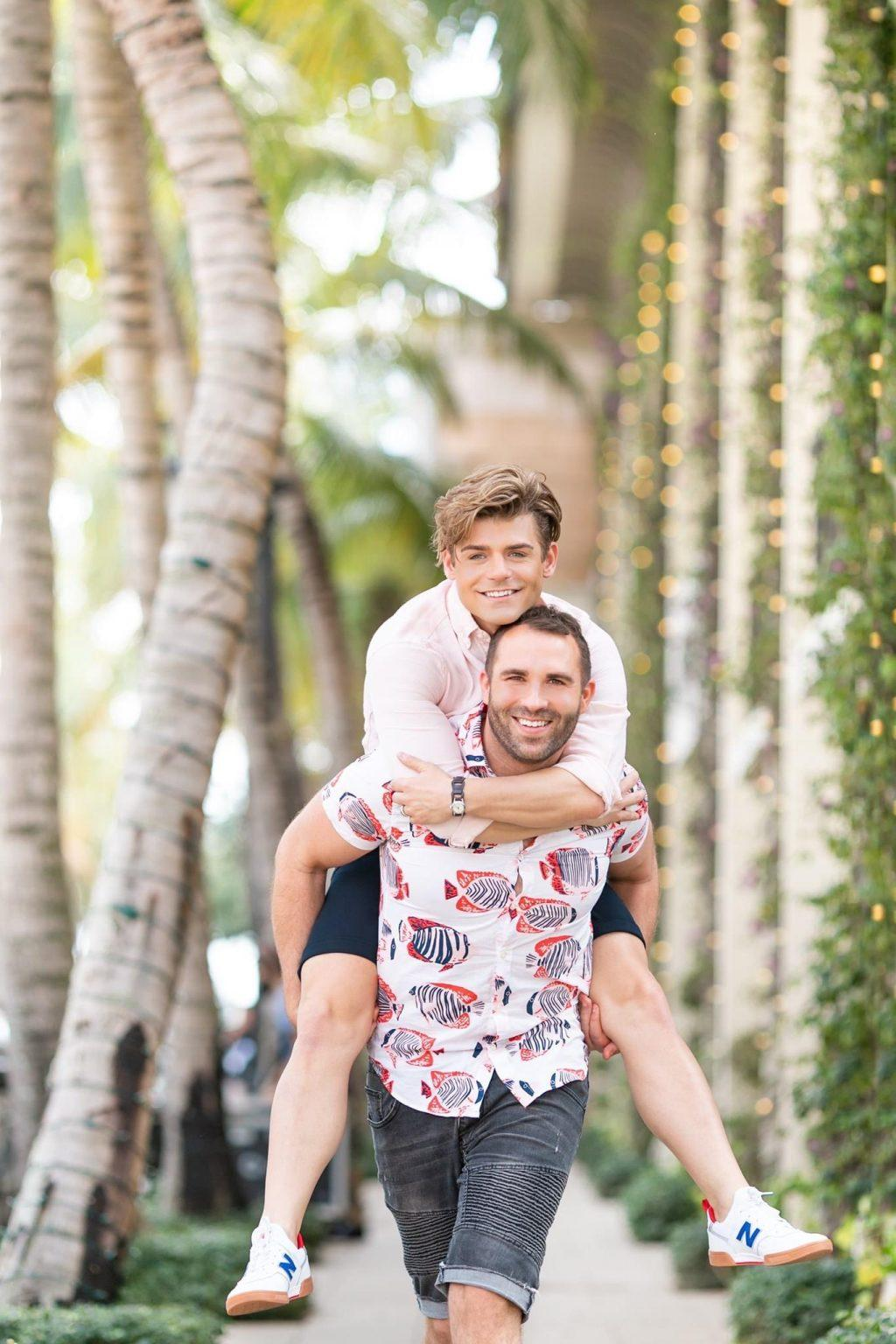 "Knight gives Clayton a piggy back ride near Aneé Atelier in Palm Beach, Fla. in March. In July, the couple created an LGBTQ+ channel titled ""A Gay in the Life."""