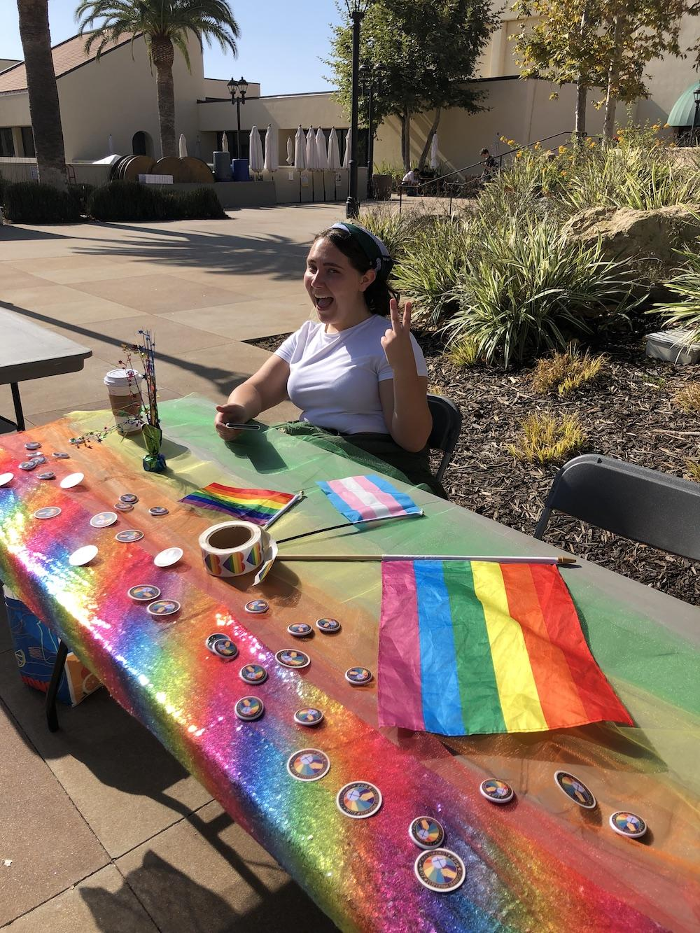 Buffaloe holds up the peace sign in 2019 at a booth for Crossroads Gender and Sexuality Alliance. She said she has made a lot of great connections through the club and hopes to continue mentoring children.