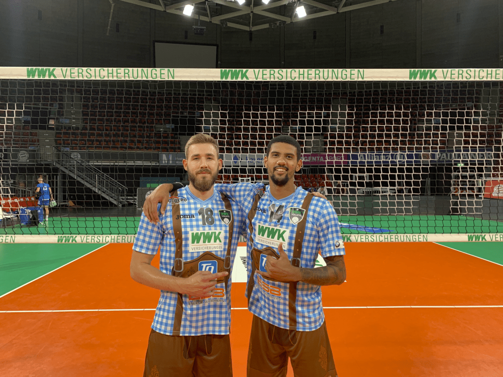 Wieczorek (left) poses with teammate Jalen Penrose in front of the net in their lederhosen jerseys while playing in Munich's Audi Dome in September. The lederhosen jerseys became popular in the volleyball community across Europe. Photo courtesy of Dave Wieczorek