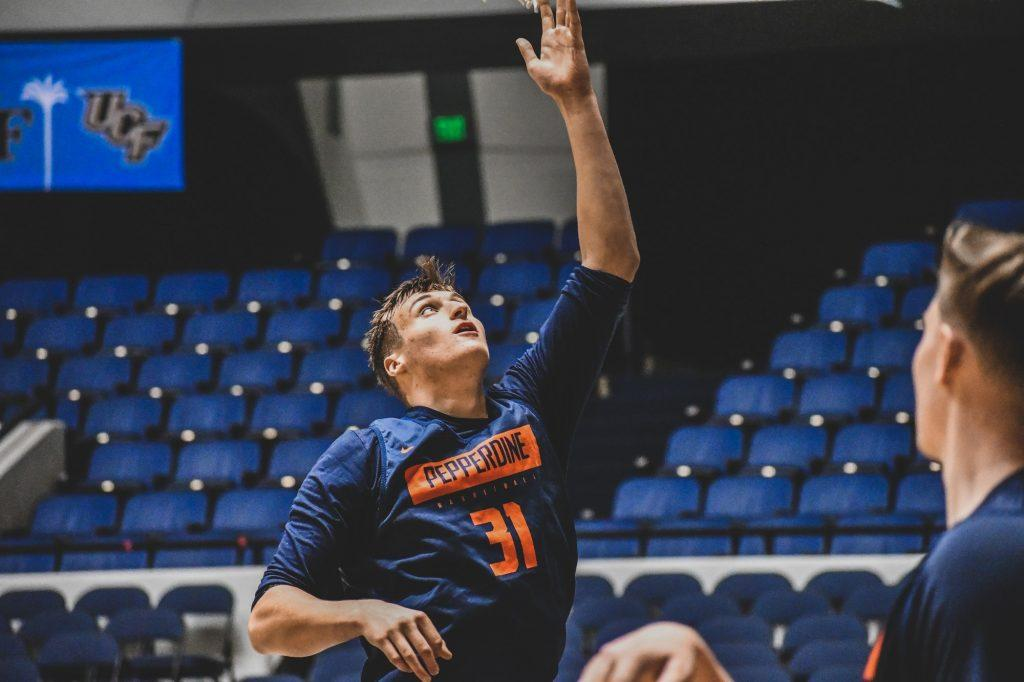 Sophomore forward Jan Zidek softly reaches to lay the ball on the rim for an easy two while warming up for a Wooden Legacy tournament game Nov. 25, 2019. Zidek played sparingly last season but may have a much larger role this year. Photo courtesy of Morgan Davenport, Pepperdine Athletics