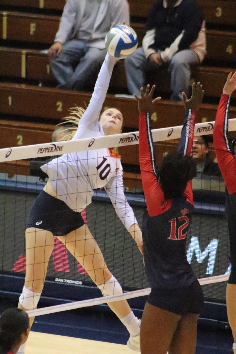Senior outside hitter Shannon Scully goes up for a kill against a blocker from Saint Mary's University on Nov. 14, 2019. The Waves swept the Gaels at home for their eleventh league win. File photo