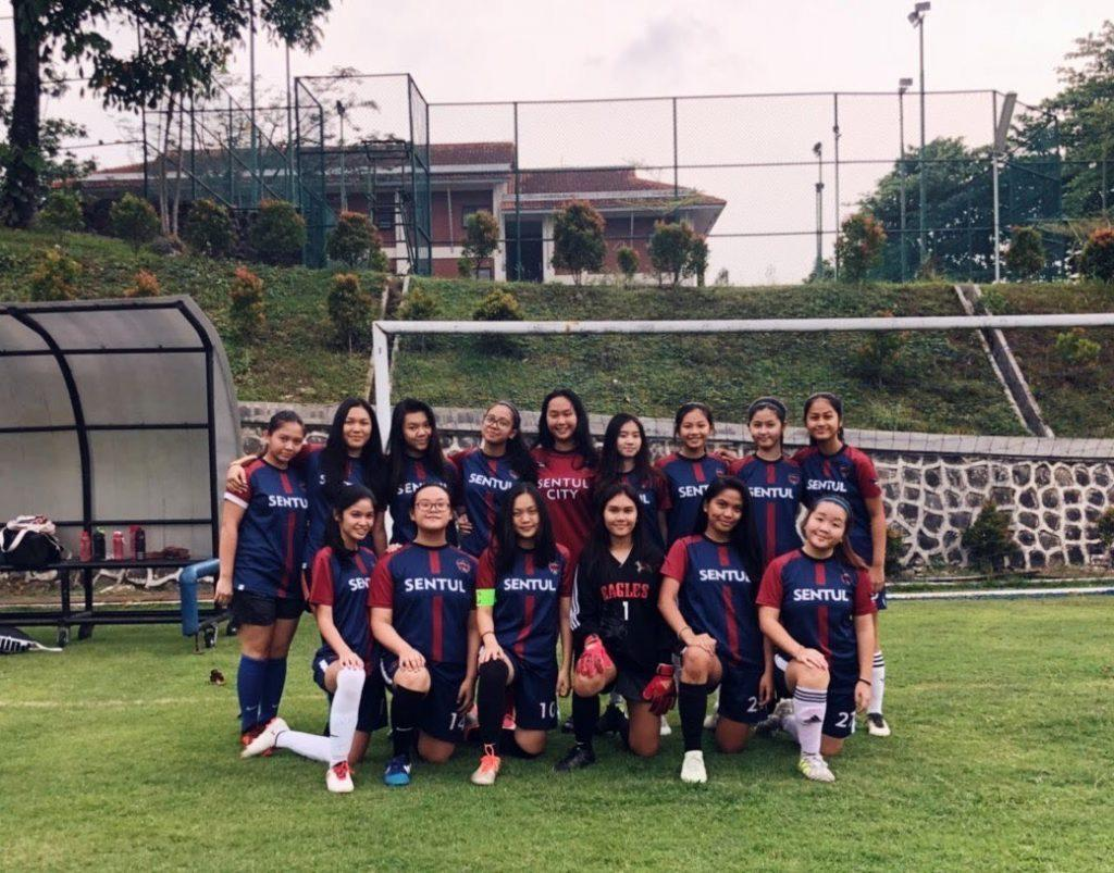 Putri (front row, third from left) kneels with her soccer teammates for a group portrait. During her middle and high school years, Stella spent her time playing soccer.