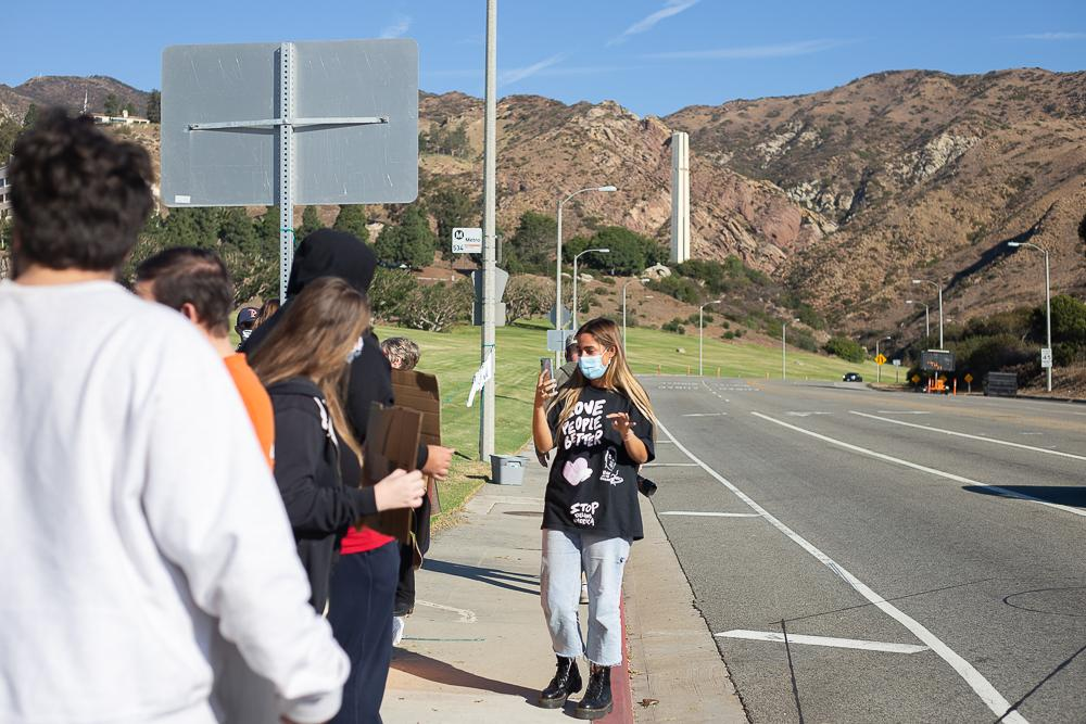Hope Dease films a group of students protesting on Malibu Canyon Road for Pepperdine Justice Coalition's Instagram live. Dease said seeing the small community protesting Nov. 11, brought her hope. Photo by Ashley Mowreader