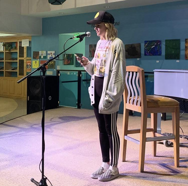 Senior Olivia Smith reads an original poem at the 2019 fall coffeehouse event. Cooper said sometimes students would come in for Jamba Juice and leave having read their original work. Photo courtesy of Amanda Cooper