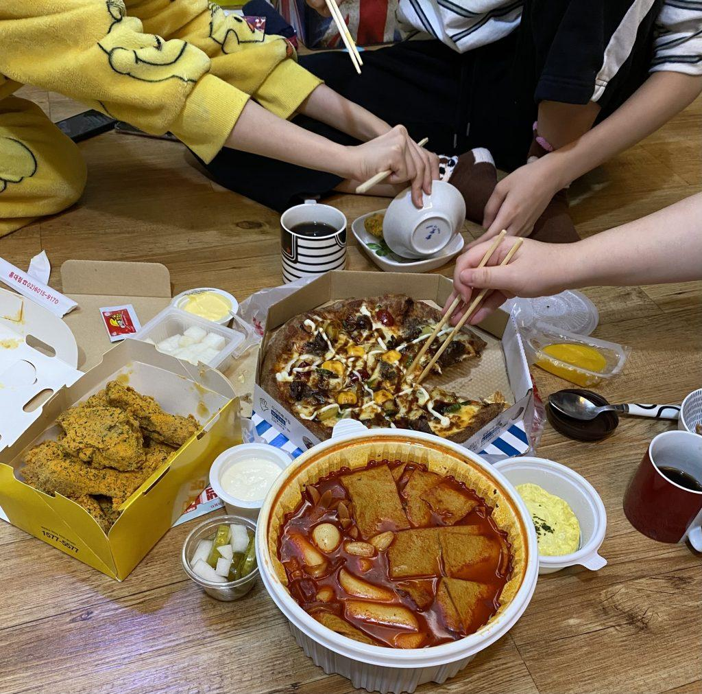 A few of my housemates dig into pizza and fried chicken Oct. 16 at our share house. Feasting from the white bowl, we ate spicy Ddukkbokki, a popular traditional Korean food that consists of rice cakes, fish cakes, eggs, vegetables and the Ddukkbokki sauce.