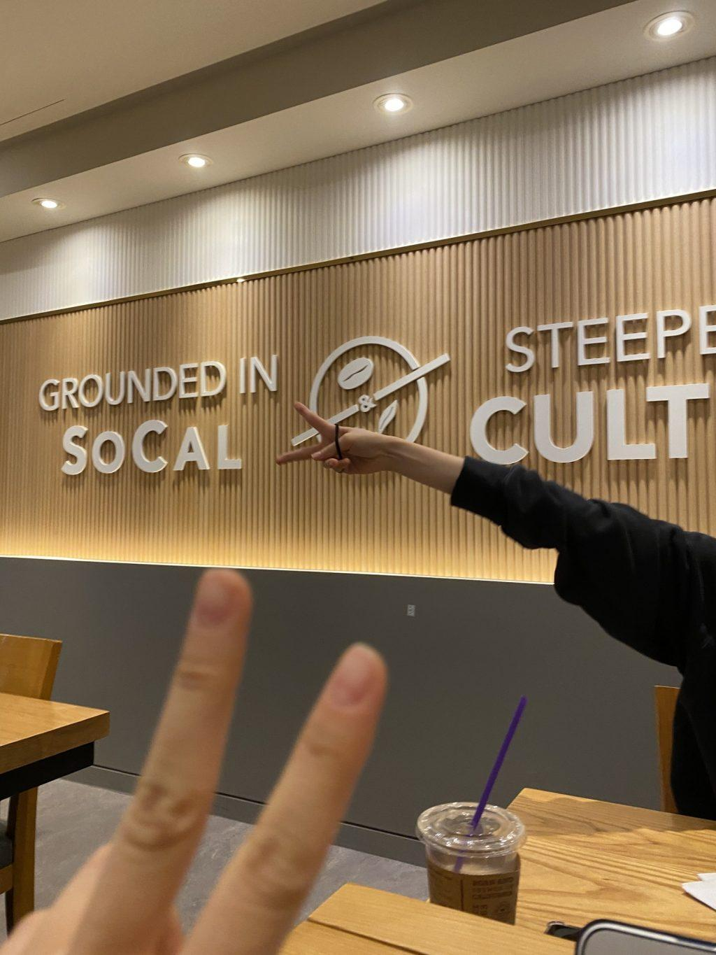 "My roommate and I hold up peace signs while taking a break from our online studies at a local Coffee Bean on Oct. 24. I was reminded of home with the ""Grounded in SoCal"" sign on the wall and the American music playing inside. Photo by Claire Lee"
