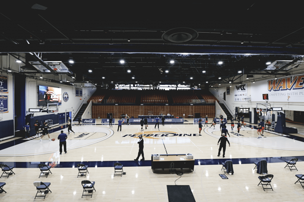 The Pepperdine Waves (right) warm up opposite of the Pilots for another fanless game in Firestone Fieldhouse on Jan. 16. ///I think it would be cool to include how many games were fanless in Firestone this year, if you end up using this photo///