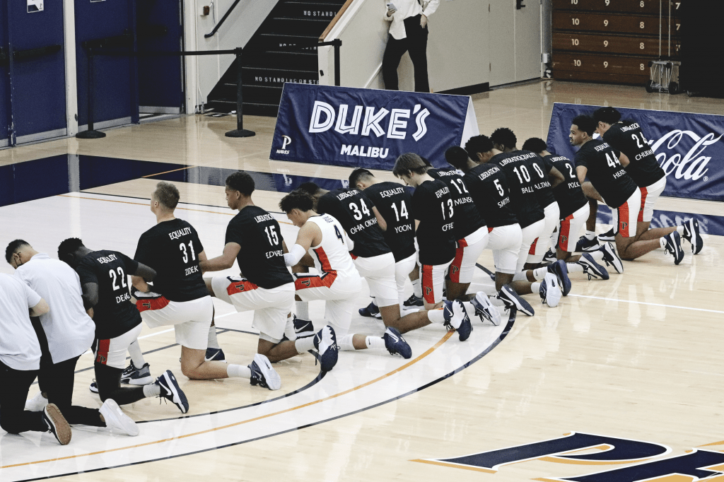 All 14 men's basketball players kneel for the national anthem before defeating Pacific University on Jan. 21 game at Firestone Fieldhouse.