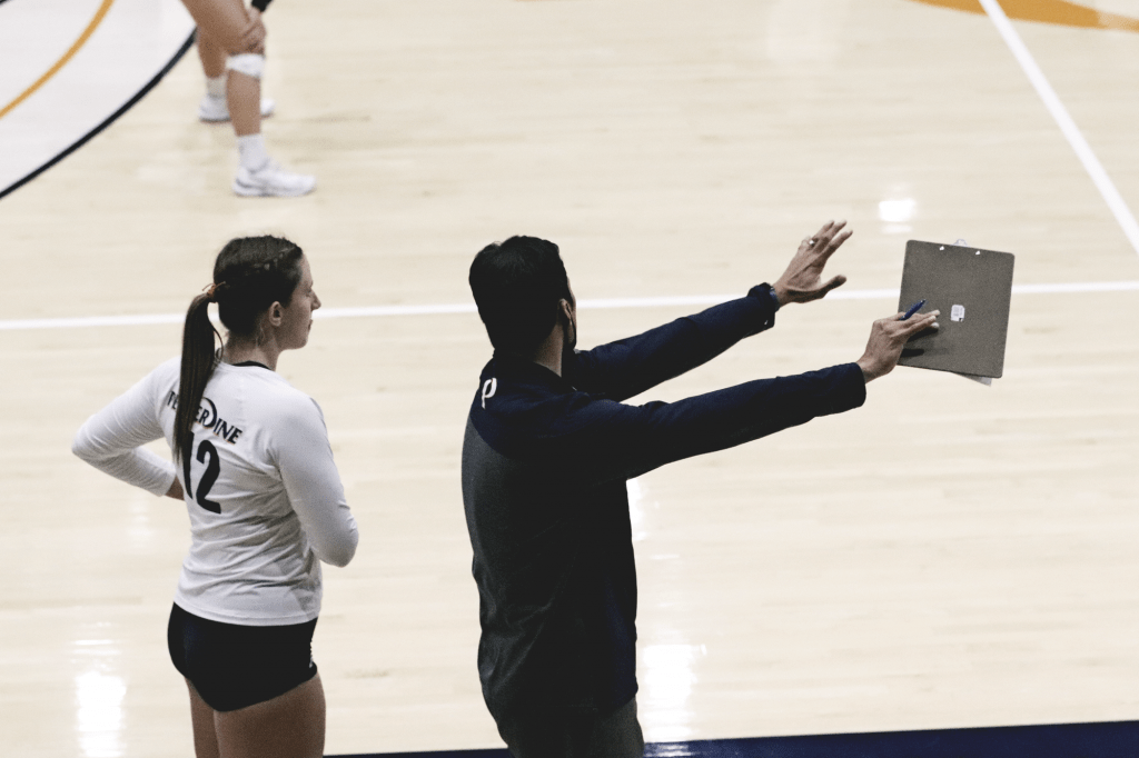 Brown (left) receives instruction from Head Coach Scott Wong (right) at Firestone Fieldhouse on Feb. 16. Brown has been a strong force for the Waves during her freshman year.