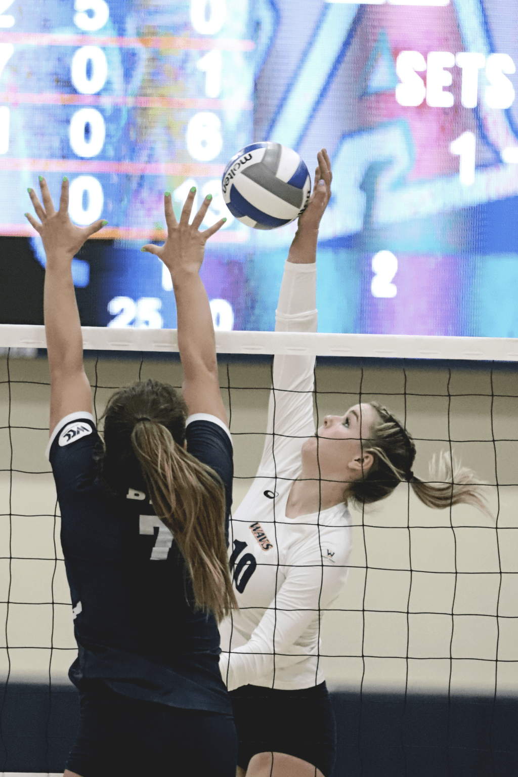 Scully reaches over the Cougar Block. The senior stepped up in the third match of the night, ending with the most kills (18) of the match.