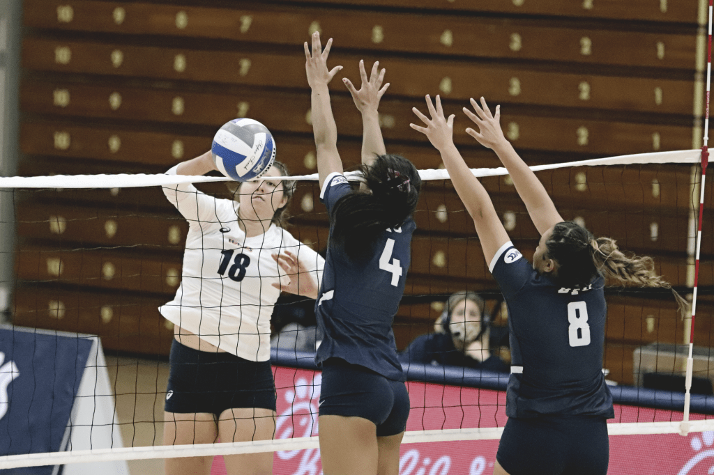 Junior outside Rachel Ahrens swings past the BYU block. Ahrens racked up 14 kills over the course of the match, hitting a .333 average.