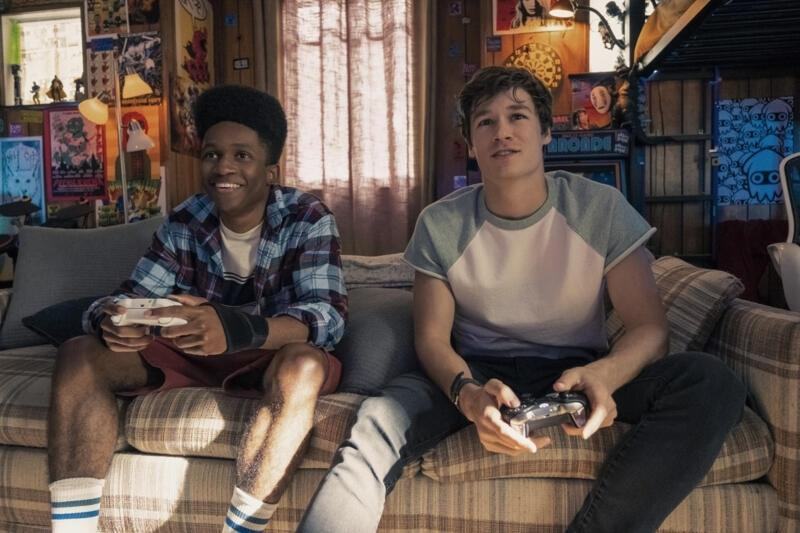 Mark (right) and his friend Henry (Jermaine Harris) play video games. Mark told him about the time loop, but Henry does not understand the idea of it.