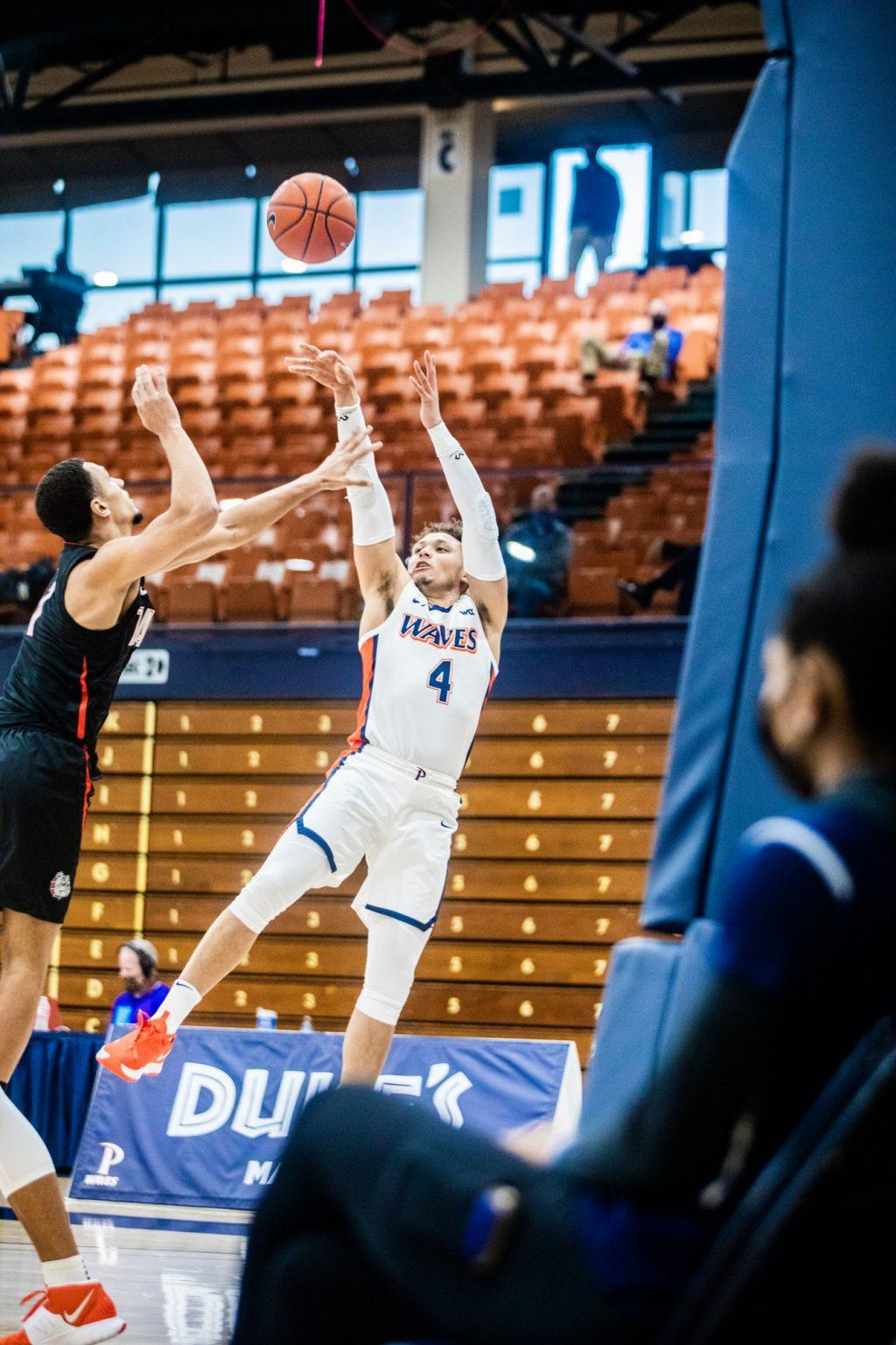 Pepperdine senior point guard Colbey Ross attempts a fadeway jump shot over Gonzaga's Jalen Suggs during the first half Saturday at Firestone Fieldhouse. Ross finished with 16 points in the game, surpassing 2,000 points in his Pepperdine career along the way.
