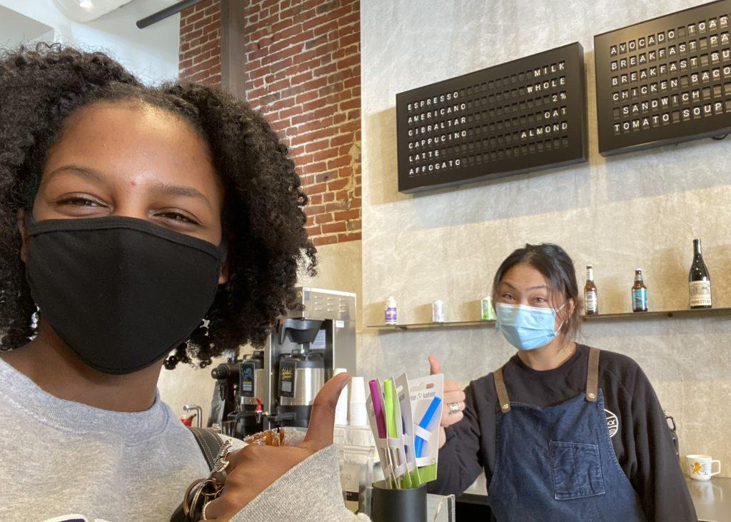 Abaya (right) smiles as her friend visits her at work in January, in Redwood City. She said her go-to drink is a cold brew, but she loves to make hot lattes with cool designs.