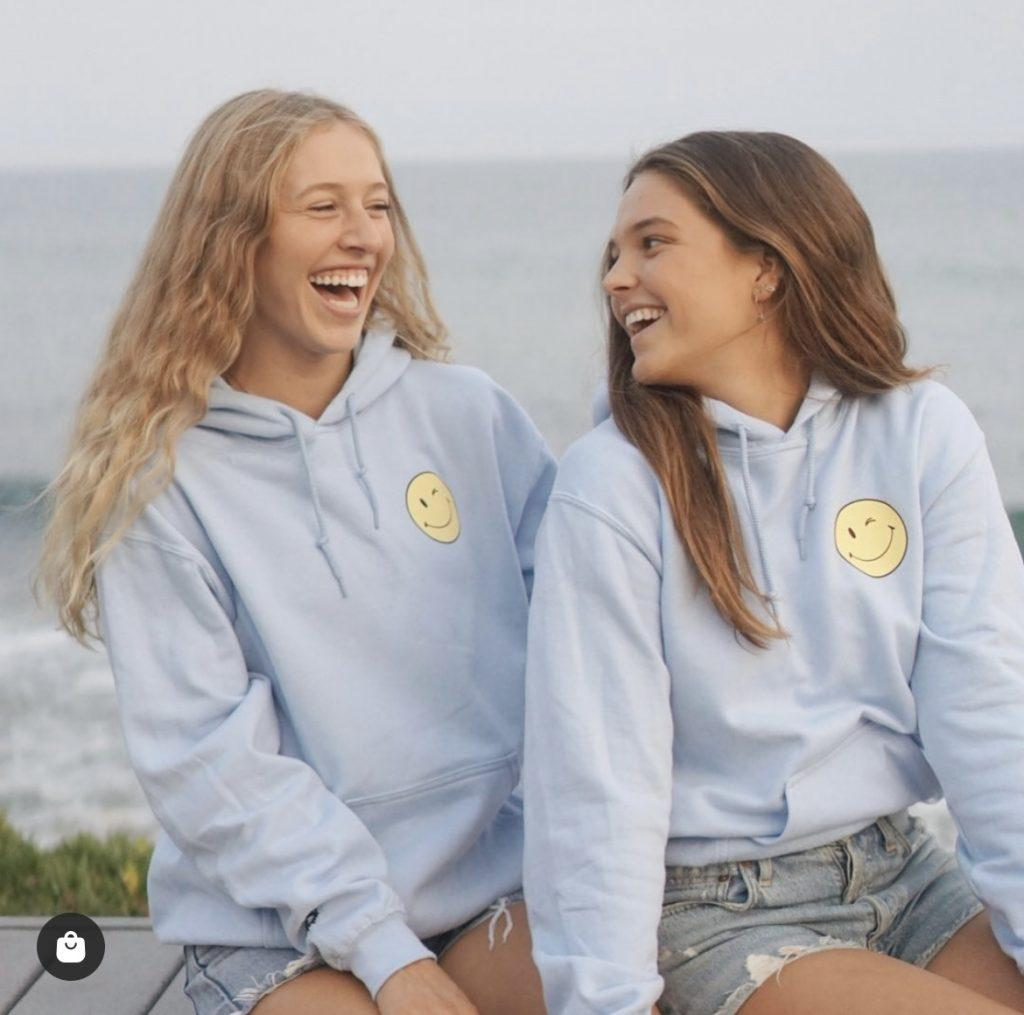 Gearhart's sorority sisters, first-year Alexa Wright (left) and Huff (right), laugh while wearing their smiley face sweatshirts in Malibu in September. After moving to Malibu, Gearhart said the location made it easy to take promotional photos and it was nice having her friends by her side.