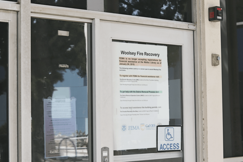 A Woolsey Fire Recovery poster dons a door panel at the Malibu Courthouse on March 24. Since the Woolsey Fire of 2018, City Council streamlined the permit process for original homeowners to rebuild, saving residents more than $4.2 million to date.