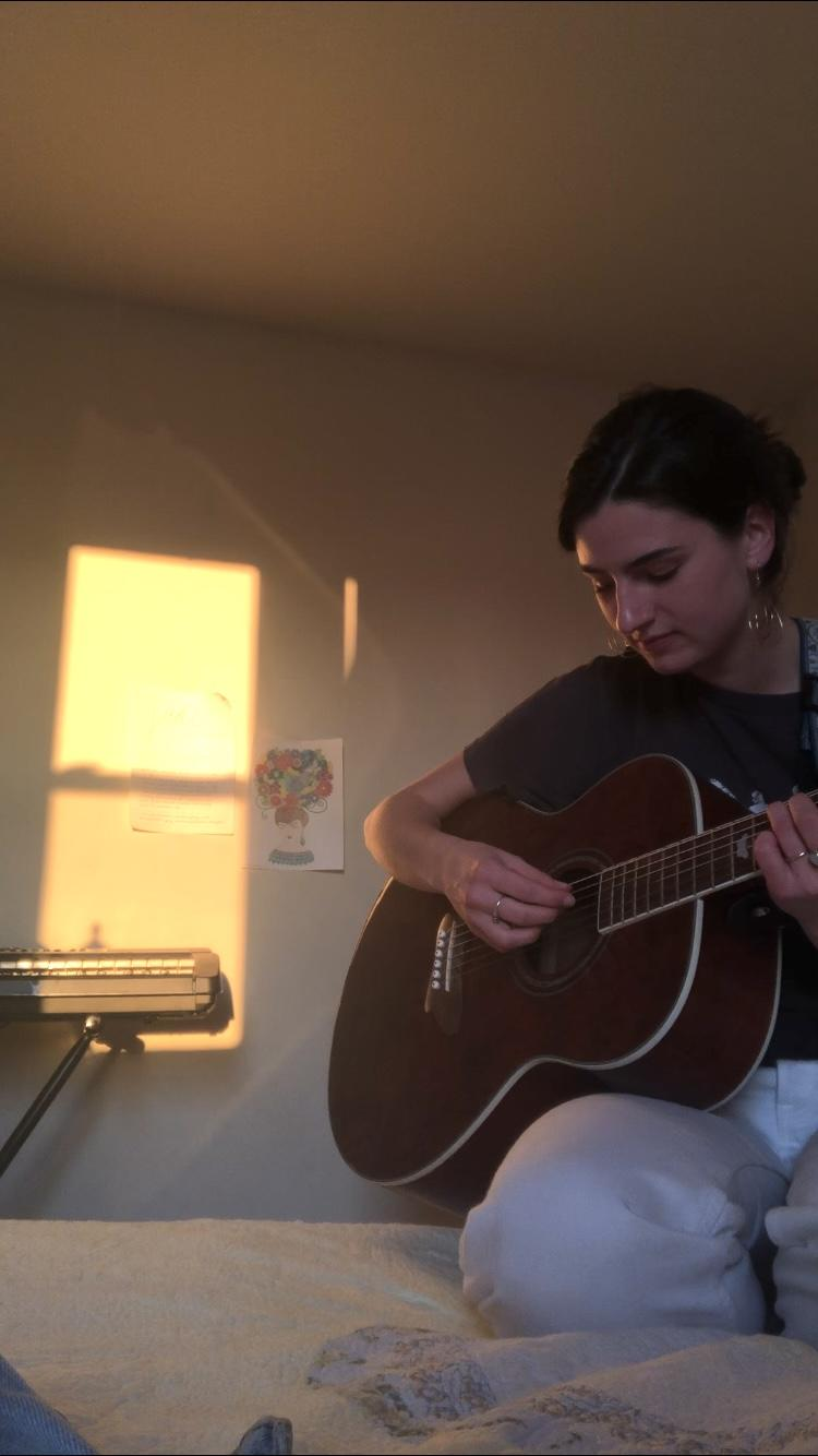 Sullivan plays a song on the guitar in her home in Fredericksburg, Va., in April. She said she was insecure about sharing her music in high school but opened up musically once she felt comfortable at Pepperdine. Photo courtesy of Lindsey Sullivan
