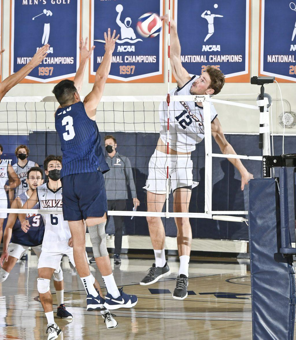 Redshirt sophomore outsider hitter Jacob Steele rolls the ball over BYU's Wil Stanley on Friday in Firestone Fieldhouse. Steele tallied nine kills in each match of the doubleheader. Photo Courtesy of Martin A. Folb | Pepperdine Athletics
