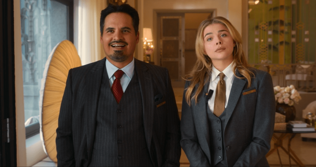 Terence, played by Michael Peña, and Kayla, played by Chloë Grace Moretz, discuss wedding plans in a hotel suite. Throughout the film, they stay busy making sure the high-profile ceremony goes just as planned.